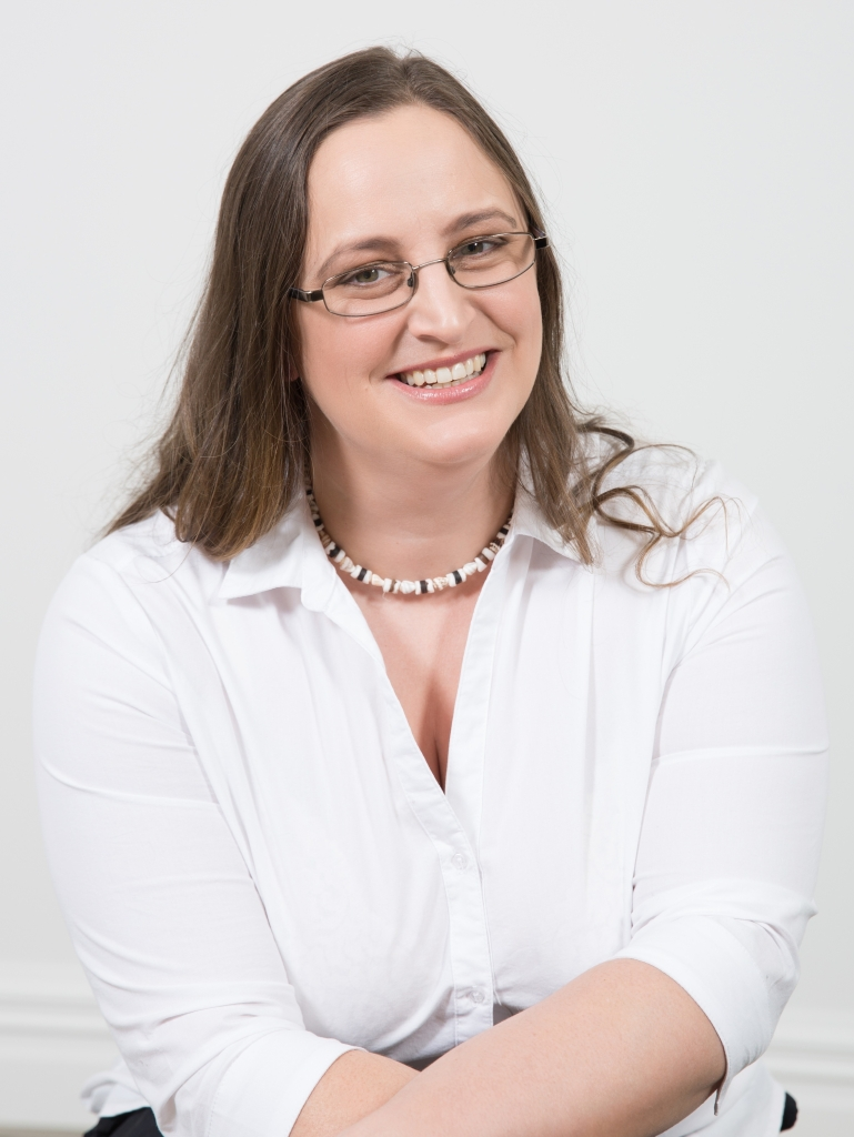 Smiling woman with brown hair and glasses in a white shirt.
