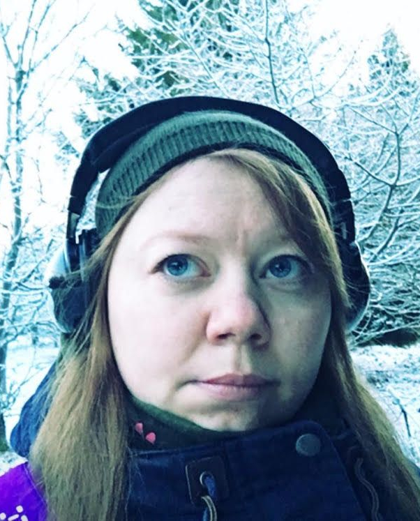 Woman outdoors with light brown hair, blue eyes, headphones and knit hat looking upwards,